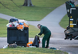 © Licensed to London News Pictures. 18/04/2021. London, UK. A council worker collects litter overflowing form a bin on Primrose Hill in North London, despite the park being closed from 10pm last night. A curfew has been put in to place at the park over the weekend  to prevent large gatherings in the evening. Photo credit: Ben Cawthra/LNP