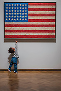 A young visitor is attracted to Flag, 1958 - Jasper Johns: 'Something Resembling Truth' at the Royal Academy of Arts. The exhibition spans over 60 years from his early career, up to the present and includes over 150 works. The show runs at the RA from 23 September – 10 December 2017.