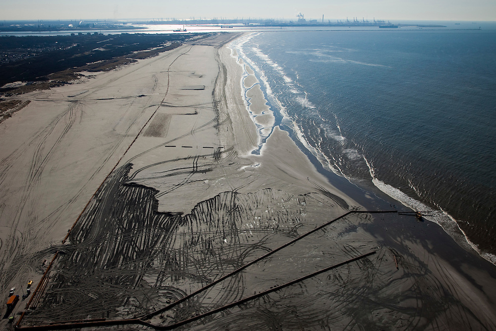 Nederland, Zuid-Holland, 's-Gravenzande, 18-03-2009; Versterking van de kust van Delfland tussen Slag Beukel en Slag Vluchtenburg. In de voorgrond de zandpersleidingen waarmee zand op het strand gespoten is, de zogenaamde zandsuppletie. De kust tussen Hoek van Holland en Den Haag is een van de 'Zwakke Schakels' in de zeewering. Verder is het strand richting Hoek van Holland extra verbreed om een nieuwe duinenrij met duinvallei te maken, natuurcompensatie in verband met de aanleg van de Tweede Maasvlakte. Maasvlakte en ingang nieuwe Waterweg aan de horizon..Strengthening of the coast of Delfland between Hoek van Holland and The Hague by means of sand-supplementation. Pipes for transport of sand in the foreground. Extra sand has been applied to make an extra dune valley on the beach. This so-called nature compensation is necessary because of the construction of the nearby Maasvlakte 2 (land reclamation for Port of Rotterdam). Maasvlakte and entrance Port of Rotterdam / Nieuwe Waterweg at the horizon..Swart collectie, luchtfoto (toeslag); Swart Collection, aerial photo (additional fee required); .foto Siebe Swart / photo Siebe Swart