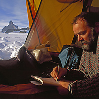 Queen Maud Land, Antarctica.Writing in a notebook in a tent with the Ulvetanna peak beyond.