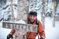 A backcountry skier poses behind the famed Steeple trail sign in the Mt Mansfield backcountry, near Stowe, Vermont
