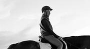 A mature senior riding a horse against the sky.