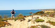 One woman walking on cliffs above the Atlantic Ocean on coastal long distance footpath trail, The Fisherman's Walk or Ruta Vicentina, near Zambujeira do Mar, Alentejo Littoral, Portugal, Southern Europe. To her side is the painted way-mark sign for the route.
