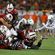 Louisville Cardinals running back Dominique Brown (10) is tackled by the Miami defense during the NCAA Football Russell Athletic Bowl football game between the Louisville Cardinals and the Miami Hurricanes, at the Florida Citrus Bowl on Saturday, December 28, 2013 in Orlando, Florida. (AP Photo/Alex Menendez)