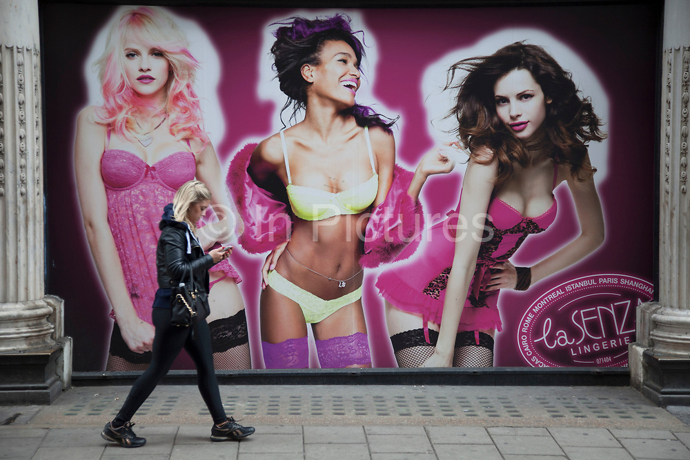 People passing large advertising for lingerie company in central London. La Senza use these skinny and skantily clad young women to advertise their underwear designs.