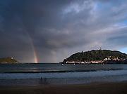A rainbow and stormy skies out at sea, seen over La Concha Bay at San Sebastian, Spain