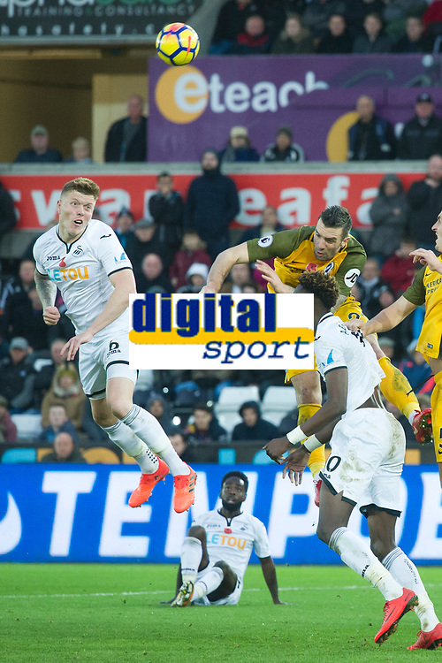 Football - 2017 / 2018 Premier League - Swansea City vs. Brighton & Hove Albion<br /> <br /> Alfie Mawson of Swansea City heads at goal, at The Liberty Stadium.<br /> <br /> COLORSPORT/WINSTON BYNORTH