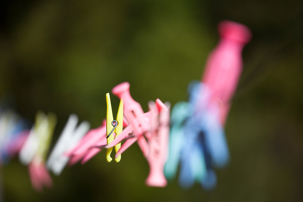 Colorful clothes pins on a clothes line in New Zealand with very shallow depth of field focus