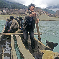 CHINA, TIBET, Tsangpo River Gorge. Boatman rows pilgrims to holy waterfall in one of earth's deepest canyons.