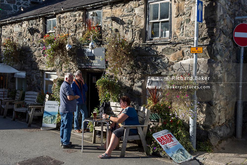 Pub drinkers and smokers enjoy evening sunshine outside the Torrent Walk pub, on 12th September 2018, in Dolgellau, Gwynedd, Wales.