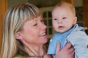 Margaret (Linda) Gundlaugsdottir of the Thoroddson family at home in Hafnarfjordur, near Reykjavik, Iceland, with her grandson. A revisit, after the family was profiled in Material World in 1993. MODEL RELEASED..