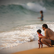 Protective father giving confidence to his daughter for her first sea baptism...