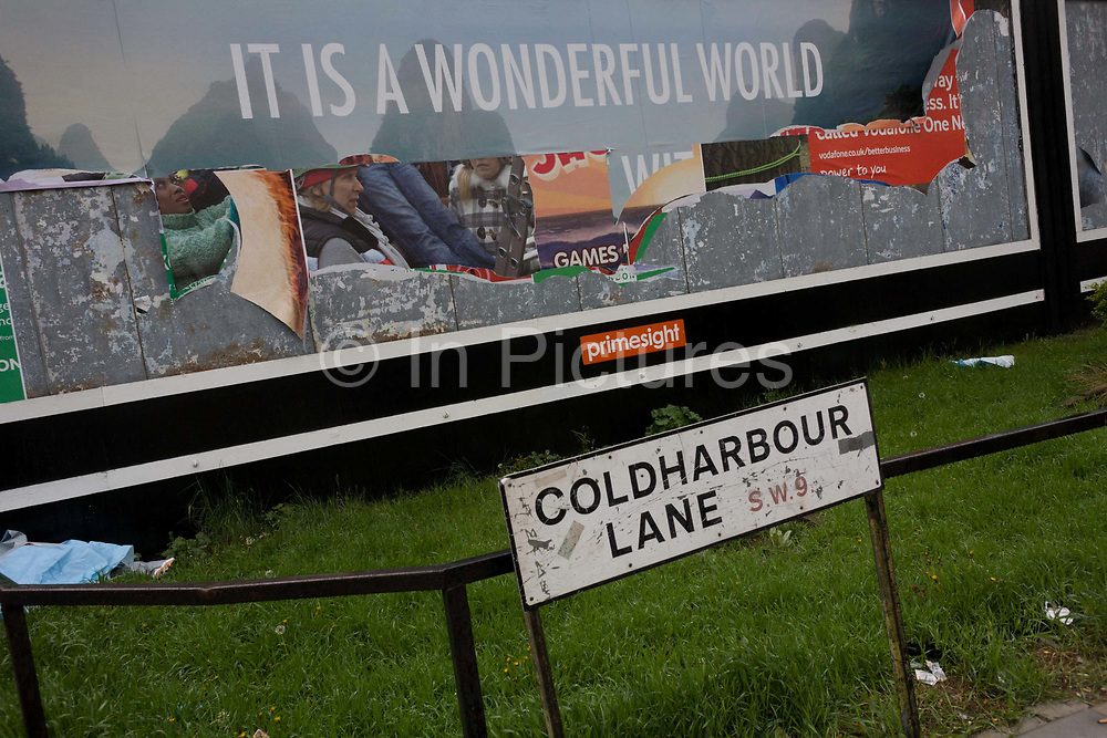 """A peeling billboard reveals older layers of Primesight street advertising incl the dystopian message """"It's a wonderful world."""" The differences between dream and dystopia make for a comical, if slightly sad landscape in this south London street called Coldharbour Lane SW9, the home for housing estates and problem families in the borough of Lambeth. Peeling sheets of past ad campaigns after rainfall has helped tear the top layer to reveal others underneath. <br /> Primesight is one of the UK's leading Outdoor advertising companies with ownership of a diverse portfolio of products in a range of environments."""