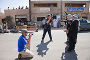 A photographer films some of the actors at Medina Wasl, a fabricated Iraqi village used for training soldiers deploying to Iraq at Fort Irwin, California, in the Mojave Desert.
