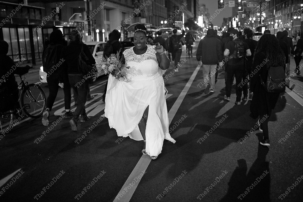 PHILADELPHIA, PENNSYLVANIA:  CHRISTINA HOLLY, a bride to be, walks through a demonstrators during a black lives matter protest near Center City in Philadelphia, Pennsylvania. They were protesting police brutality in Philadelphia.  (Credit Image © Brian Branch-Price/TheFotoDesk)