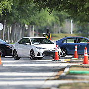 Vehicles line up to gain access to a drive through testing facility for the Coronavirus (COVID-19) at the Orange County Convention Center on Friday, March 27, 2020 in Orlando, Florida. (Alex Menendez via AP)