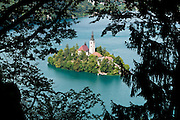 Trees frame a romantic church isolated on a lake island. The town of Bled and glacial formed Lake Bled (Slovene: Blejsko jezero) are popular tourist sites in the Julian Alps in northwestern Slovenia. The lake surrounds Bled Island (Blejski otok, the only natural island in Slovenia), upon which stands the Pilgrimage Church of the Assumption of Mary (Slovenian: Cerkev Marijinega vnebovzetja), built in the 15th century and now popular for romantic weddings. Lake Bled hosted the World Rowing Championships in 1966, 1979, 1989, and 2011.The lake is 35 kilometers from Ljubljana International Airport.