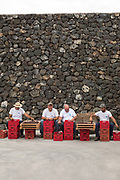 Men destem grapes by hand from red crates in front of a stone wall on Pantelleria, off Sicily in Italy.