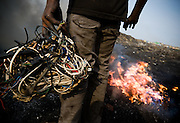 A boy holds a ball of cables that came from computers and other electronics as he intends to burn them to extract copper that can be sold for money near the Agbogboloshie market in Accra, Ghana on Thursday August 21, 2008.