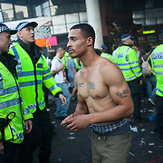 A man striped naked to his waiste with tattoos, one of them in memory of his late nan.Portobello Road is heaving with people at sunset after the parade has finished. A large number of police in riot gear is present to controle the crowd. The Notting Hill Carnival has been running since 1966 and is every year attended by up to a million people. The carnival is a mix of amazing dance parades and street parties with a distinct Caribbean feel.