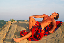 Nude man with a blanket reclining on rocks in California