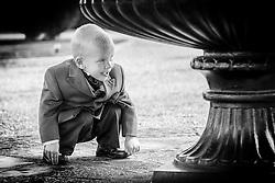Boy at wedding playing hide and seek.