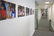 Posters of children playing next to glass access barrier in main corridor