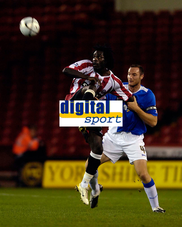 Photo: Jed Wee.<br /> Sheffield United v Birmingham City. Carling Cup. 24/10/2006.<br /> <br /> Sheffield United's Ade Akinbiyi (L) tries to control the ball as Birmingham's Martin Taylor marks him.
