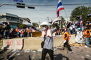 """03 DECEMBER 2013 - BANGKOK, THAILAND: Anti-government protestors celebrate tearing down a government barricade in Bangkok. Thousands of anti-government protestors entered the government offices in the Dusit district of Bangkok Tuesday after police stopped using tear gas and water cannons on the protestors. Protestors marched through the district waving Thai flags and chanting """"long live the King!"""" Suthep Thaugsuban, leader of the protest movement, called it a partial victory but vowed to continue his battle to bring down the government of Yingluck Shinawatra.     PHOTO BY JACK KURTZ"""
