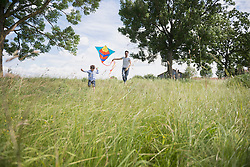 Father and his son running with kite in the countryside, Bavaria, Germany