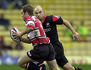 Watford, GREAT BRITAIN, 3rd April 2004, Vicarage Road, ENGLAND. [Mandatory Credit: Photo  Peter Spurrier/Intersport Images],<br /> 03/04/2004  - 2003/04 Zurich Premiership - Saracens v Gloucester<br /> James Simpson-Danielrunning with the ball, Saracens Paul Bailey moves in for the tackle.