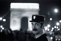 ca. December 31, 1974, Paris, France --- Police Officer With Arc de Triomphe in Background --- Photograph by Owen Franken