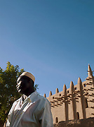 A man talks on the streets outside the Great Mosque of Djenné, the worlds largest mud built structure and UNESCO heritage site, at Djenné, Mali