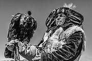 Portrait of Kazakh eagle hunter with his eagle (Aquila chrysaetos) in black and white, Altai Mountains, Bayan Ulgii, Mongolia