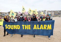 """© Licensed to London News Pictures; 11/06/2021; St Ives, Cornwall UK. G7 summit in Cornwall. """"Birdgirl"""" MYA-ROSE CRAIG (right) marches with a banner at a protest by Extinction Rebellion in St Ives on the first day of the G7 summit. Photo credit: Simon Chapman/LNP."""