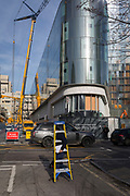 A man carrying stepladders walks past construction on the development called One Blackfriars on the Southbank, on 30th January 2018, in the south London borough of Southwark, England.