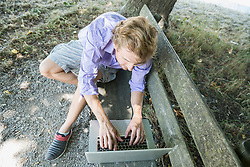 Mid adult man using laptop on bench