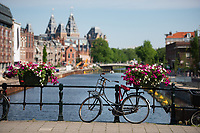 The canal bridges are decorated with  fresh flowers and plenty of locked bikes in Amsterdam, Netherlands.
