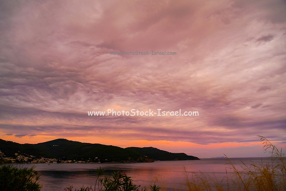 Beautiful purple, orange, red and blue sunset over Poros Island, Greece. Poros is a small Greek island-pair in the southern part of the Saronic Gulf, Greece