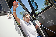 """June 13 - PHOENIX, AZ: ROBERT LUNA, from Anaheim, CA, dressed as US President Barrack Obama waves to the crowd as he gets off a bus in Phoenix before an immigrants' rights rally and vigil. About 40 immigrants' rights activists from Anaheim, California, joined Phoenix area activists at the Arizona State Capitol Sunday for a prayer vigil and rally against SB 1070, the Arizona law that gives local law enforcement agencies the power to ask to see proof of immigration status in the course of a """"lawful contact"""" and when """"practicable."""" Immigrants' rights and civil rights activist say the bill will lead to racial profile. Proponents of the bill say it is the toughest local anti-immigration bill in the country and merely brings state law into line with federal immigration law.  The law, which was signed by the Arizona Governor in April, goes into effect on July 29, 2010.   Photo by Jack Kurtz"""