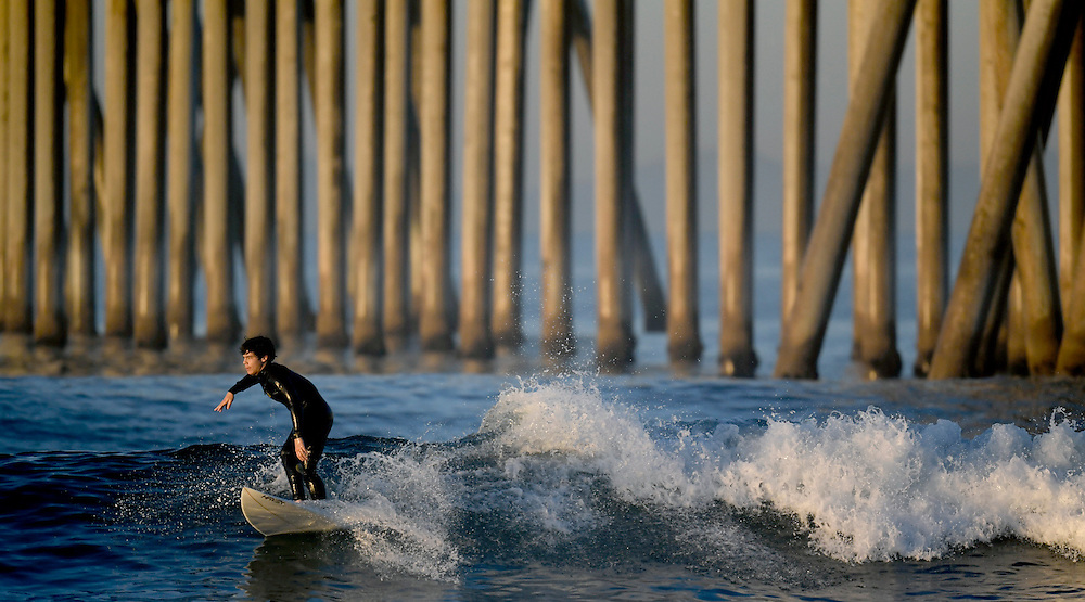 A surfer rides a wave on a sunny morning at Huntington Beach in Southern California on Thursday.
