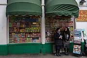 Two Jehovah's Witnesses stand with copies of the Watchtower magazine next to a shop window of assorted snacks on shelves in a corner shop (convenience store) on Gerrard Street, Chinatown, on 5th March 2018, in London, England.