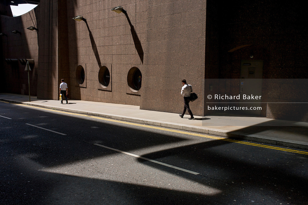 Strangers walk through urban landscape of modern architecture at Broadgate in the City of London.