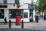 Outside the Cock Tavern in Somers Town on 1st July 2016 in London, United Kingdom. Somers Town, a district in north west London, is a large housing estate nestled between Euston, St Pancras and Kings Cross Library. Predominantly filled with social housing for the past 200 years, much of the area's housing was built in the twentieth century by the local authority.