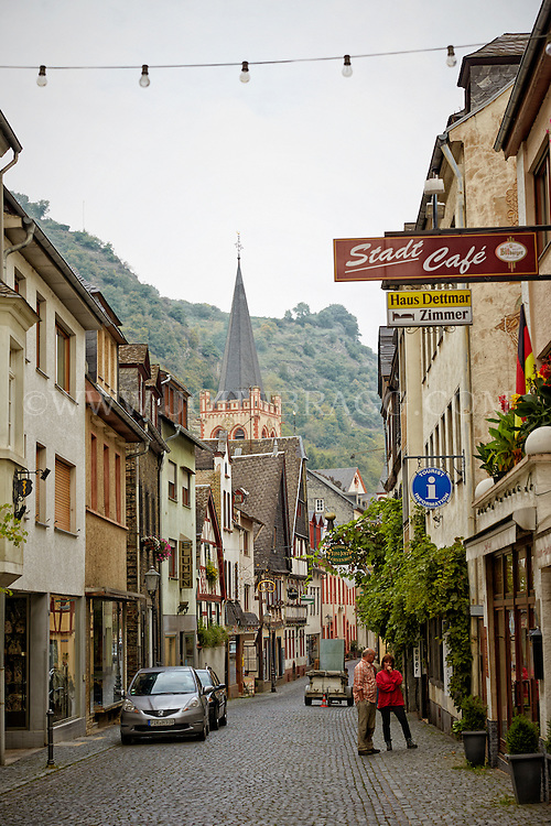 View of a cobblestone street with St. Peter Church and mountains in the background, Bacharach, Germany.