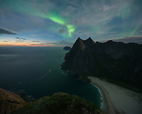 Northern lights shine in sky over Horseid beach, Moskenesøy, Lofoten Islands, Norway