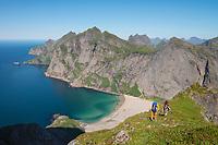 Two female hikers ascending mountain ridge above Bunes beach, Lofotodden national park, Moskenesøy, Lofoten Islands, Norway