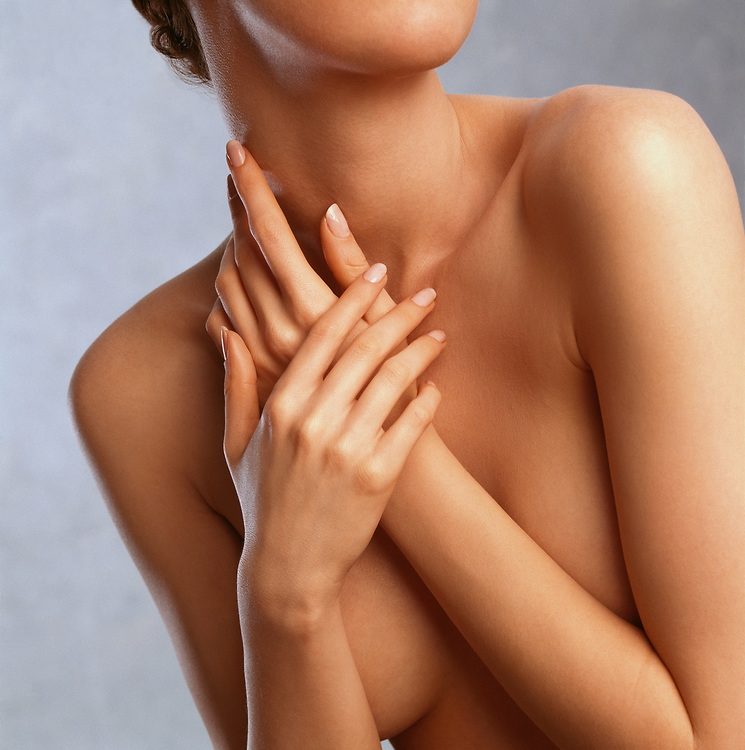 Skincare photo of nude woman's flawless body with hands in front of breasts