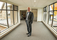 "Reverend Dr. Warren Bouton stands in the newly finished ""bridge"" connecting the Congregational Church with the office complex.  (Karen Bobotas/for the Laconia Daily Sun)"