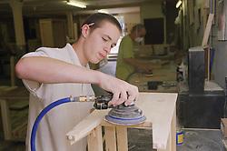 Cabinet maker sanding down bedside cabinet using D A Sander,
